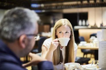 Trinkende Frau beim Frühstück im Restaurant West