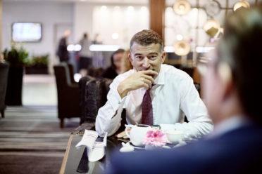 Lachender Mann während einem Geschäftsmeeting